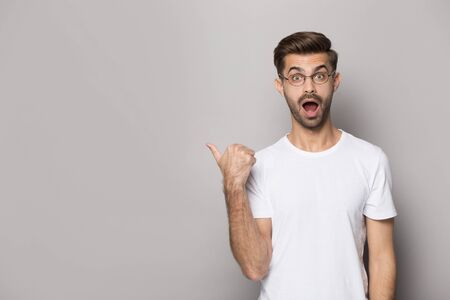 Amazed funny guy wearing white t-shirt glasses point finger aside at copy space advertise better offer huge discount opportunity, eye vision correction procedure, good services, isolated on beige wall Stok Fotoğraf