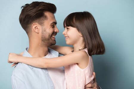 Loving daddy look at little adorable daughter feeling love isolated on blue studio background profile faces side view, deep devotion warm relationships, love care, closest person, fathers day concept Stock Photo