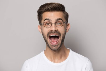 Head shot studio portrait funny guy wearing glasses white t-shirt screaming look at camera open mouth pose isolated on beige grey background, stunning news, celebration excitement lucky moment concept