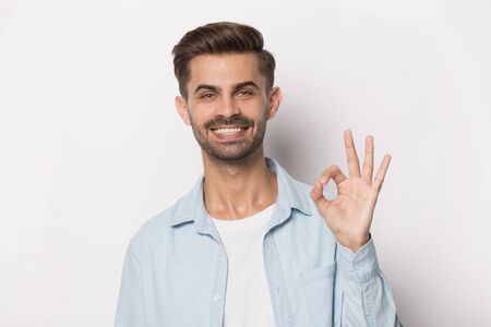 Head shot studio portrait isolated on grey background guy having hollywood smile, dental clinic client showing ok sign satisfied by dental services, whitening bleaching professional procedure concept