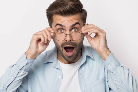 Shocked guy wearing glasses open mouth isolated on white, millennial man lowering spectacles looking at camera feel amazement cant believe in his eyes, low price, better offer eyewear store ad concept Stok Fotoğraf