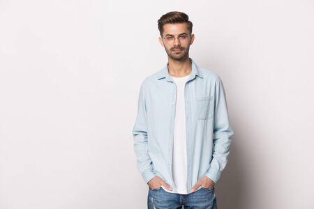 Serious handsome guy wearing glasses casual stylish clothes pose on white or grey studio background, caucasian millennial man holding hands in jeans pockets looking at camera feeling confident concept