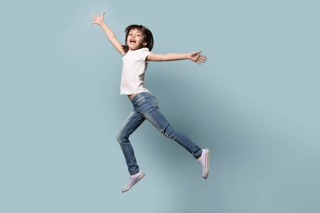 Full length funny active six years old little girl wearing casual clothes jeans white t-shirt gumshoes flying jumping with raised hands happy positive mood emotions isolated on blue studio background.