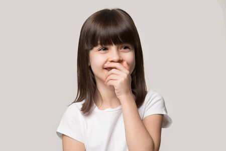 Head shot little shy brown-eyed brown-haired girl cover mouth when laughing feel embarrassment, preschool funny kid giggling stands isolated on grey studio background, have fun chuckle at joke concept