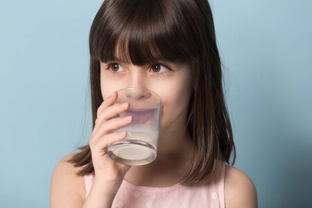 Close up portrait isolated on blue studio background little brown-haired girl holds glass drinks organic milk or yoghurt beverage get enough calcium and vitamin D, healthcare healthy lifestyle concept