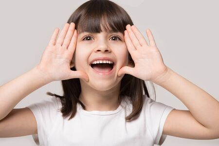 Close up portrait little brown-haired girl call somebody hold hands near face isolated on grey beige studio background, pretty kid open mouth look at camera shout speak loud make announcement concept
