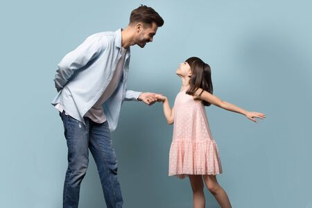 Elder brother younger sister dancing waltz enjoy time together, loving young father gentleman and little daughter princess in pink dress standing holding hands family pose isolated on blue background Stock Photo