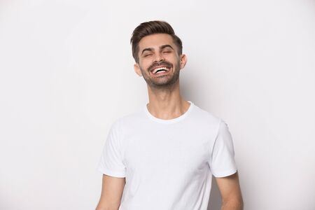 Handsome overjoyed millennial guy wearing white t-shirt laughing feeling good having great mood standing isolated on studio background, happy person, rejoice hilarious man posing indoors concept image Stock Photo