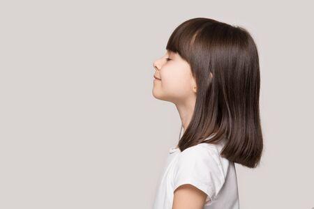 Profilo vista laterale viso ragazza dai capelli castani in piedi isolata su sfondo beige studio, bambino in età prescolare fare un respiro profondo godersi l'aria fresca o sognare riempirsi di energia sentirsi sano e buon concetto