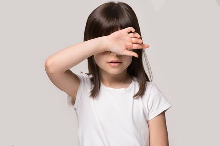 Little girl touch forehead feeling unhealthy isolated on beige studio background. Tired lack of energy preschool kid, temperature, fever flu symptoms and treatment, children medical healthcare concept