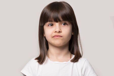 Verärgerte braunhaarige Fransenfrisur kleines Mädchen verzieht ihren Mund, fühlt sich verärgert oder unzufriedenes Kopfschussstudioporträt auf beigem Hintergrund, Konzept des frechen Kindes, Ängste des Konzepts der kleinen Person