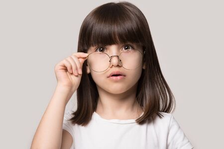 Funny little girl lowering glasses with round big spectacle frame look at camera feel amazement isolated on grey studio background head shot, confusement surprisement emotions face expressions concept Stok Fotoğraf