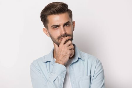 Thoughtful man holding hand on chin look at camera feeling doubtful uncertain head shot studio portrait isolated on white grey background, concept of consideration, making important difficult decision