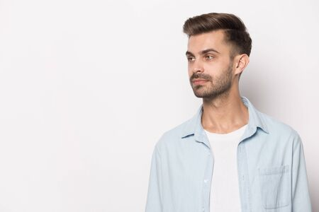 Serious handsome european appearance guy wearing casual clothes blue shirt white t-shirt looking aside at freespace copy space, bearded brown-haired stylish man isolated on white studio background Stock Photo