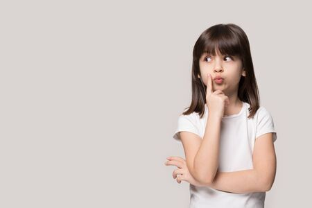 Thoughtful little girl six years old daughter look away on copy space thinking isolated on grey beige background, funny kid pout lips hold finger near mouth conceived some kind of prank, concept image