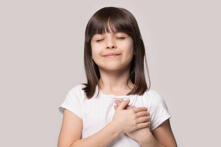 Oprecht schattig meisje gesloten ogen hand in hand op borst gevoel dankbaarheid pose geïsoleerd op zanderige kleur beige achtergrond, armen op hart gebaar van liefde waardering dankbaarheid, adoptie concept