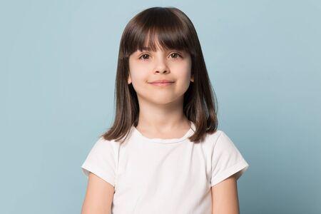 Schattig zes jaar oud meisje in wit t-shirt geïsoleerd op blauwe studio achtergrond, mooie bruinharige pony kapsel Europese uitstraling kind pose binnen lachende blik op camera, generatie Z concept Stockfoto