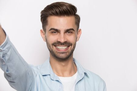 Young guy smiling looking at cam view from web camera isolated on white studio background, millennial positive man using smartphone taking self portrait makes photography modern wireless usage concept Banco de Imagens