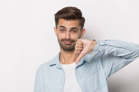 Serious european guy in casual clothes look at camera show thumbs down head shot studio portrait on grey white background, negative feedback and dislike, disagreement disapproval or rejection concept