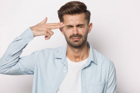 Isolated on grey white background man frown screw up his eyes puts fingers aimed to head like gun make killing himself gesture, body language symbol of big problems, unhappy desperate person concept Stock Photo
