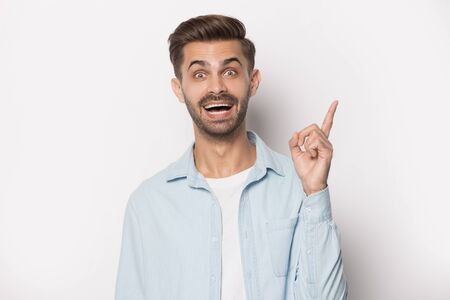 Guy raised finger up gesture of resourceful person studio shot isolated on grey background, clever funny man able to think creatively, excited with good idea, inspiration motivation brain work concept