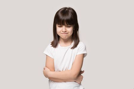 Frustrated upset lonely little girl standing in closed pose isolated on beige studio background, lonely offended brown-haired kid weeping feel unhappy, anxiety disorder or naughty bad behavior concept