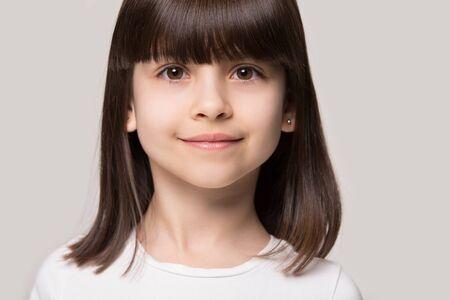 Nahaufnahme Studioporträt entzückendes braunhaariges kleines Mädchen, das die Kamera einzeln auf grauem oder beigem Hintergrund betrachtet, sechs Jahre altes gesundes positives Kind im Vorschulalter mit schönem Gesichtskonzeptbild