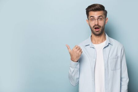 Surprised funny guy wearing glasses pointing finger aside at copy space posing isolated on blue studio background excited by unbelievable eyewear optics store offer, advertise product services concept 스톡 콘텐츠