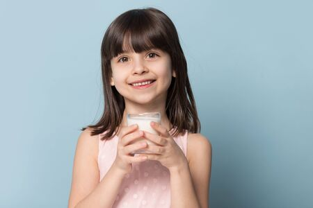 Preschool girl brown-haired adorable kid holds glass with milk source of protein, calcium and vitamin D, smiling looking at camera isolated on blue studio background, healthy habits lifestyle concept