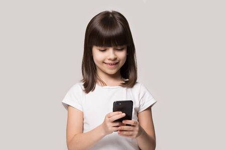 Six years old girl hold smart phone enjoy online communication with friend, play new free game use application isolated on grey beige background, parental control, gen z, modern wireless tech concept