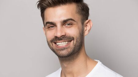 Close up portrait young man with healthy teeth beaming orthodontic white wide smile isolated on grey studio background tooth whitening procedure, happy face expressions positive emotions concept image