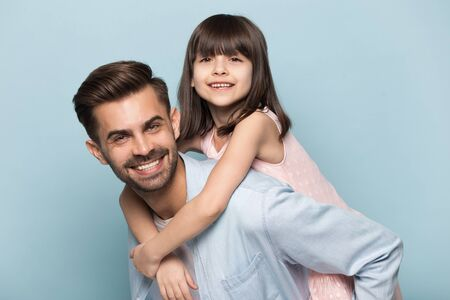 Handsome father give piggyback daughter, holding on back adorable preschool kid pose look at camera isolated on blue background. Playful people having fun, concept of loving family leisure activities Stock Photo