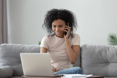 Sonriente mujer afroamericana milenaria hablando por teléfono usando la computadora portátil en la oficina en casa, feliz joven dama de raza mixta haciendo llamadas teniendo una conversación móvil mirando la pantalla de la computadora sentarse en el sofá Foto de archivo