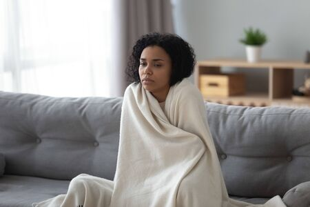 Sick young african woman feeling cold covered with blanket sit on sofa, ill black girl shivering freezing warming at home wrapped with plaid, no central heating problem, fever temperature flu concept Stock Photo