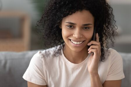 Happy young african american woman holding cell talking on the mobile phone at home, pretty smiling black girl calling boyfriend on cellphone enjoy pleasant mobile conversation on telephone indoors