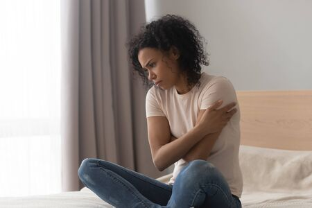 Upset depressed african woman feel hurt sad sit alone on bed, frustrated black girl thinking of loneliness, unwanted pregnancy having psychological trauma grieving troubled with problem in bedroom Banque d'images