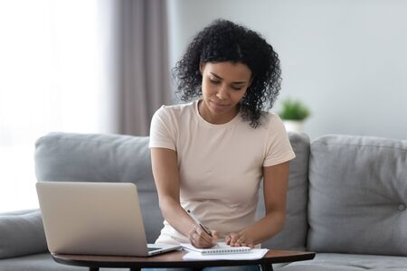 Focused african girl student study online at home making notes in notebook sit at home office desk with laptop, young black woman freelancer writing down information working distantly or e learning