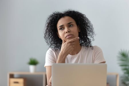 Thoughtful doubtful african female student worker looking away thinking solving problem feel lack of new creative ideas at work, pensive puzzled or bored young black woman sit at desk with laptop 스톡 콘텐츠