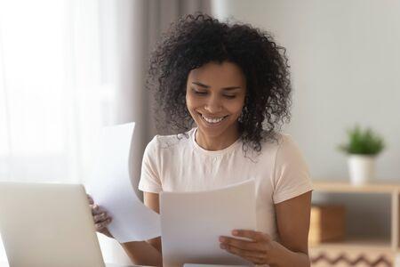 Fröhliche junge Afroamerikanerin sitzt am Tisch und liest gute Nachrichten in Papierbriefen, prüft inländische Rechnungen, lächelt schwarz und hält Dokumente, die Papierkram erledigen oder studieren, sitzen am Home Office