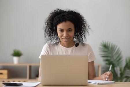 Estudiante afroamericana usa auriculares inalámbricos e aprendizaje tomando notas mirando la computadora portátil siéntese en el escritorio de la oficina en casa, niña negra estudia en línea haciendo videollamadas viendo seminarios web, educación a distancia Foto de archivo