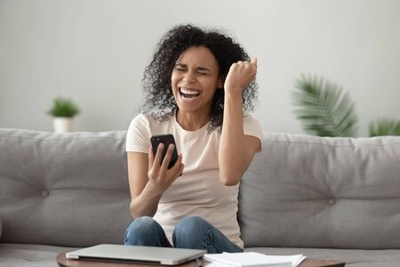 Happy overjoyed young african american woman holding mobile phone celebrating bid win game app victory sit on sofa at home, excited euphoric black girl student winner rejoicing success with cell phone