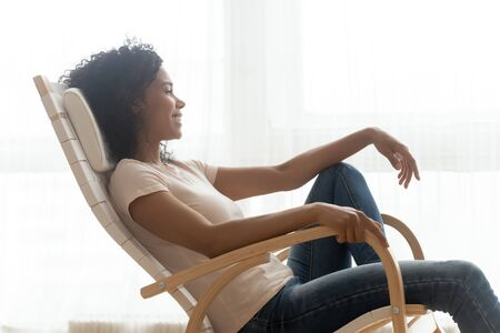 Happy calm african girl resting dreaming sit in comfortable rocking chair relaxing on cozy weekend, smiling black woman lounging enjoy peaceful quiet lifestyle feeling no stress free at comfy home Stock Photo