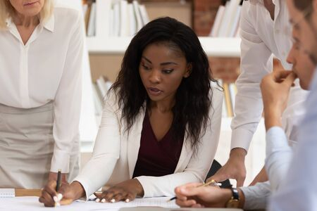 Serious african female business leader explain paperwork negotiate on contract write notes sign paper, diverse team listen to black manager analyze financial report at corporate meeting sit at table 免版税图像