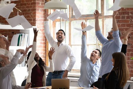 Euphoric overjoyed diverse business team tossing throwing papers celebrate success corporate victory triumph together concept in office excited by work achievement, good teamwork result at meeting