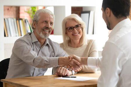 Los clientes de la feliz pareja de ancianos mayores hacen un abogado de agente de apretón de manos de un acuerdo comercial de bienes raíces de seguros financieros, clientes maduros satisfechos se dan la mano, el gerente del banco de la reunión está de acuerdo en el contrato de inversión