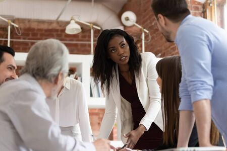 Serious female black executive discussing disputing on work issues with male caucasian colleague at corporate office briefing, business team talk solve problem brainstorm in teamwork at group meeting