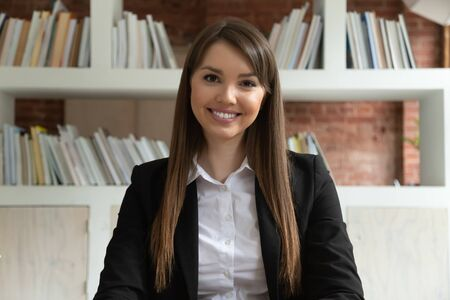 Smiling young business woman in suit coach teacher looking at camera at distant job interview, confident female professional looking at webcam talking make conference call doing internet video chat Foto de archivo - 126490150
