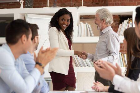 Beste werknemer concept, trotse tolerante oude senior manager baas handenschudden bevordering van belonen gelukkige Afrikaanse zwarte jonge vrouw kantoormedewerker, team applaudisseren, erkenning erkenning op het werk
