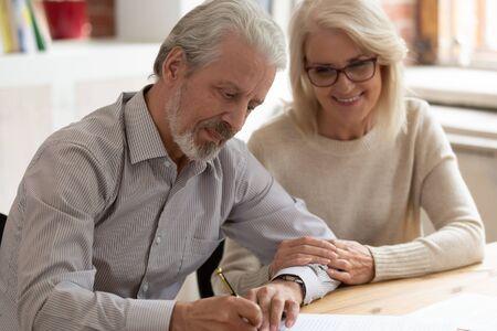 Felice coppia di famiglia più anziana marito e moglie firmano carta legale contratto di assicurazione scrivere testamento, i clienti senior mettono la firma sul documento aziendale fanno accordo finanziario prendono prestito bancario Archivio Fotografico