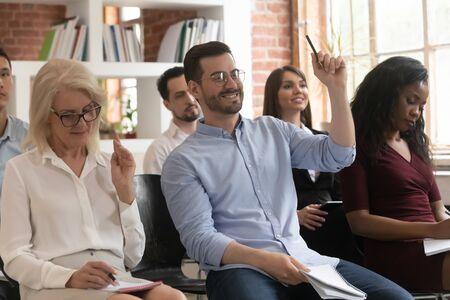 I partecipanti alla formazione del pubblico alzano le mani pongono domande alla riunione del seminario della conferenza siedono sulle sedie, il voto di gruppo degli uomini d'affari partecipa alla presentazione del seminario della conferenza della conferenza aziendale Archivio Fotografico